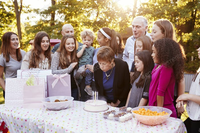 Senior woman blows out candles at her birthday garden party