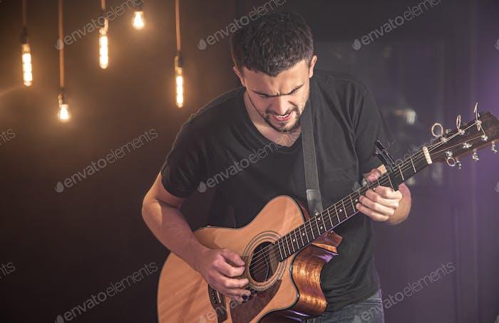 Gitarrist spielt Akustikgitarre vor verschwommenem dunklem Hintergrund beim Konzert.