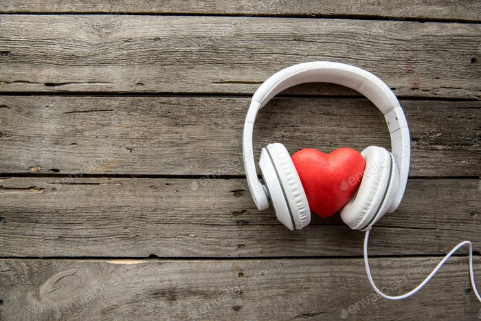 White headphones with red heart sign in the middle on wooden background