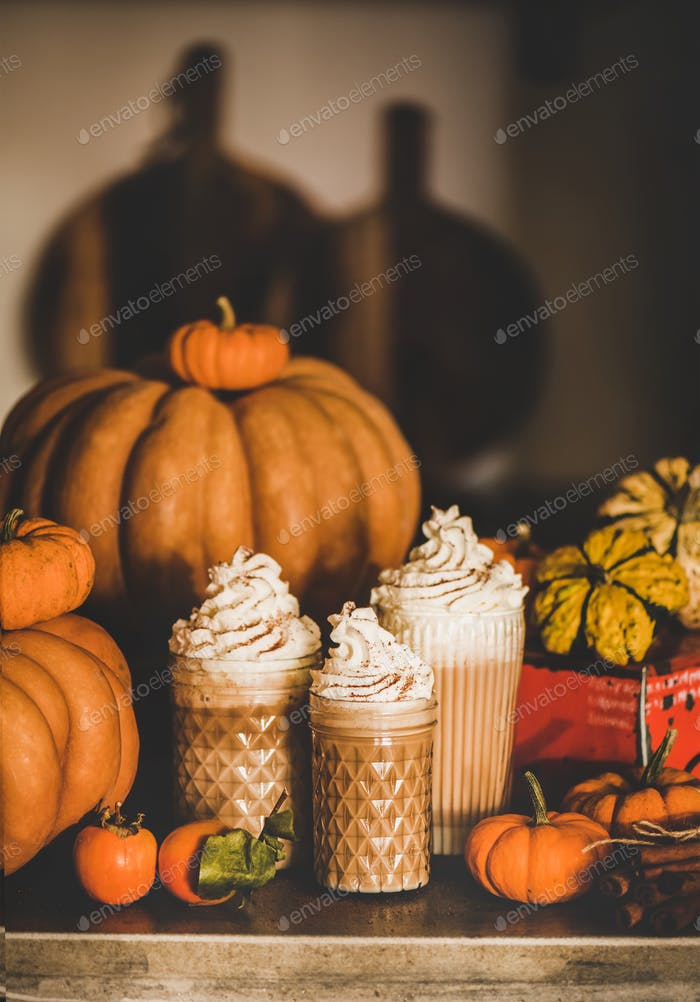 Pumpkin latte coffee decorated with whipped cream in glasses