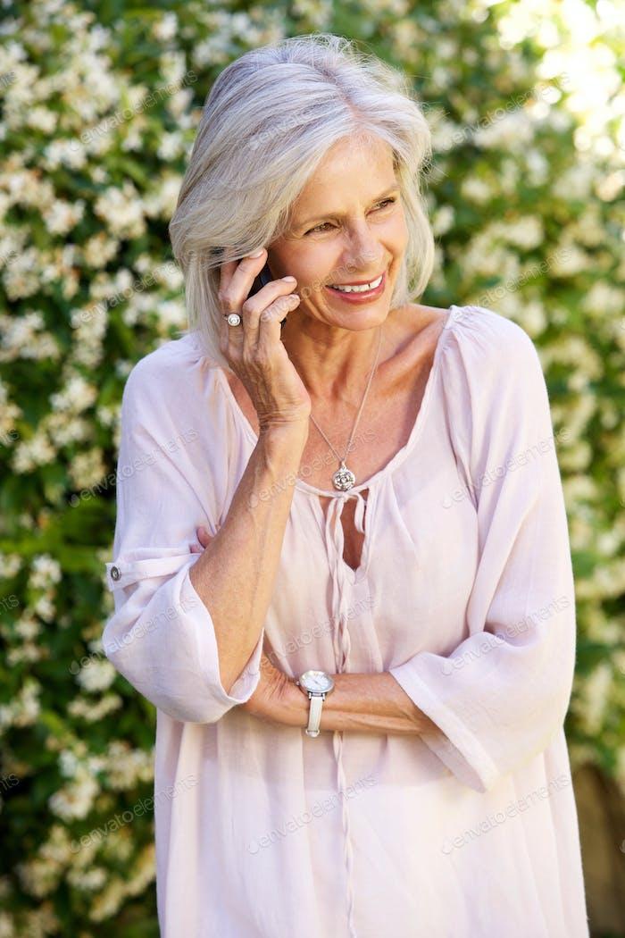 older woman talking on smart phone outside in garden