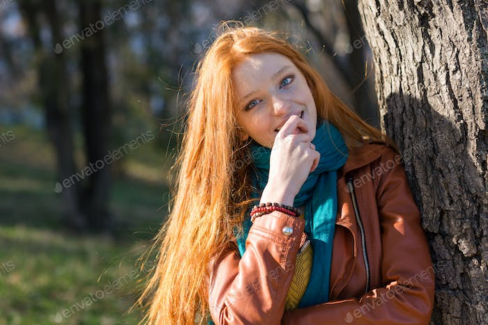 Pretty shy woman standing near the tree in park