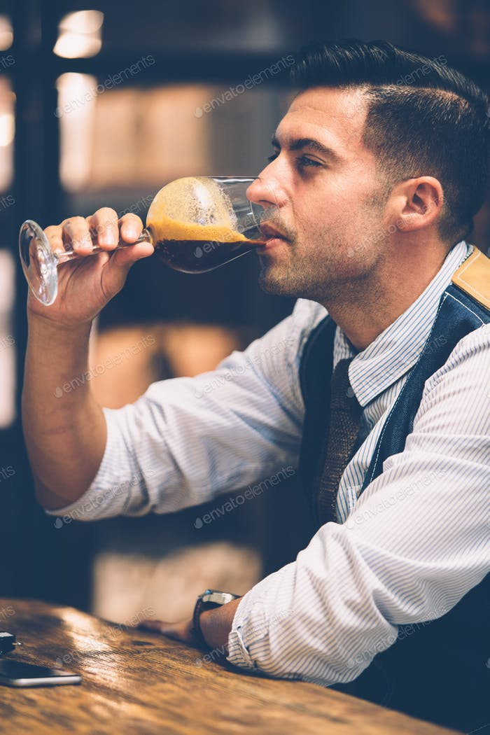 Handsome man drinking coffee from wine glass