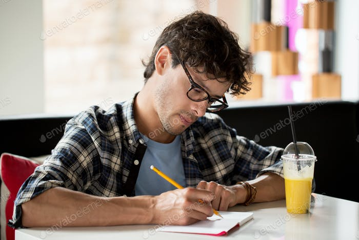 man with notebook and juice writing at cafe