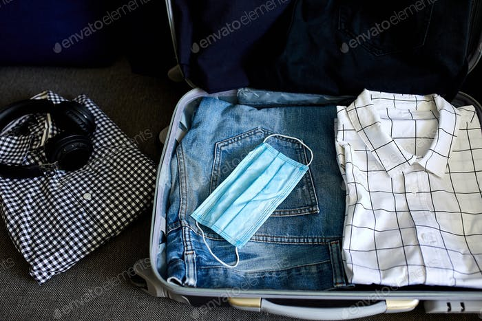 Packing suitcase at home with casual man items