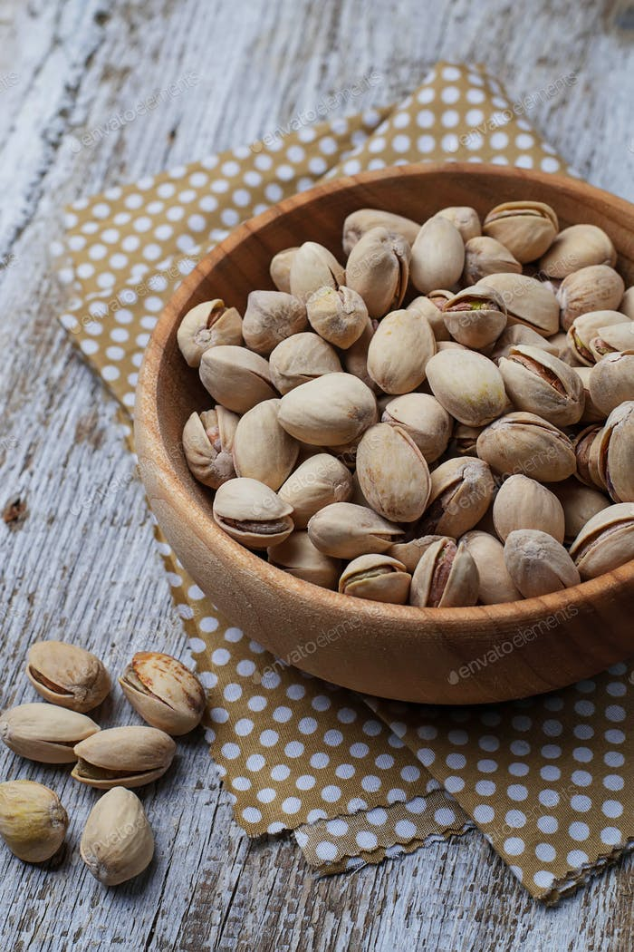 Pistachio nuts in wooden bowl