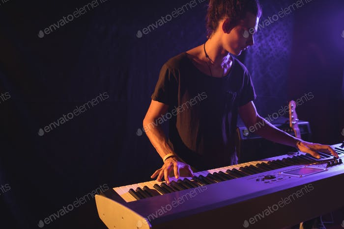 Confident male musician playing piano
