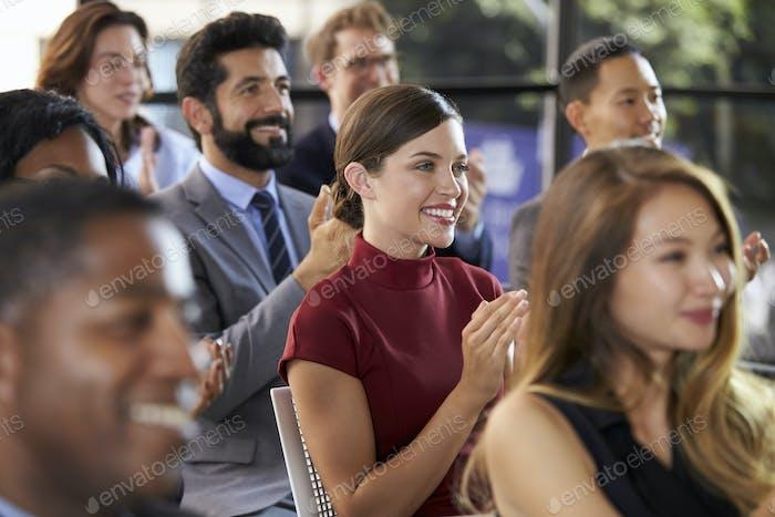 Audience applauding at a business seminar, close up