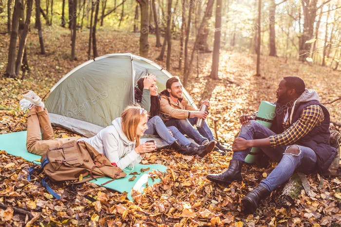 Young friends travelers sitting and talking near tent in autumn forest