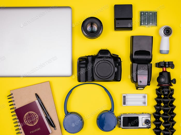 Top view flat lay of traveler accessories on yellow background
