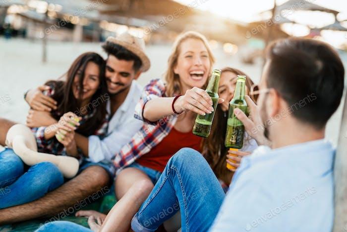 Glückliches Paar lächelnd und Bier trinken am Strand