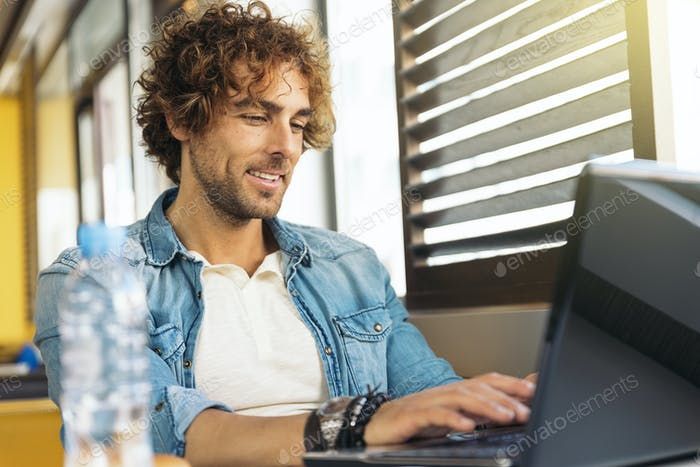 Young man using laptop while to have lunch.