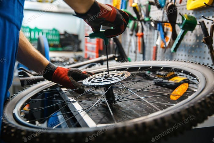 Bicycle assembly in workshop, man installs brake