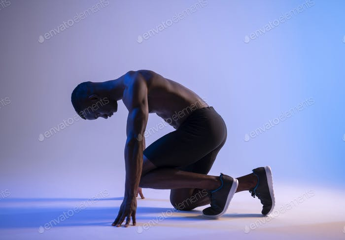 Sprinter African Muscular Man preparing for the start