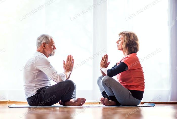 Seniorenpaar meditieren zu Hause.
