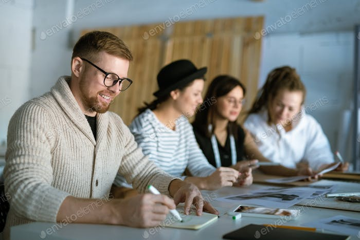 Creative fashion designer drawing sketch in copybook on background of colleagues