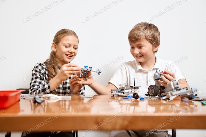 Young friends having fun, using building kit