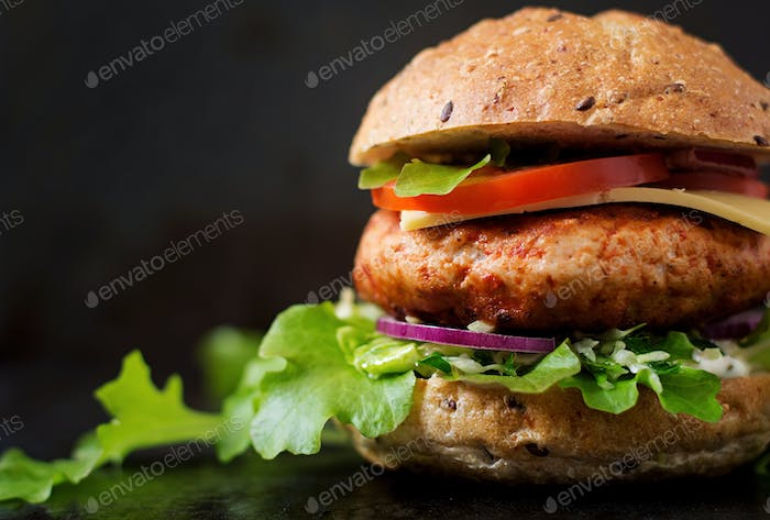 Big sandwich - hamburger with juicy chicken burger, cheese, tomato, and red onion