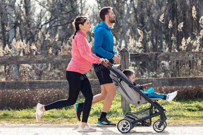 Sporty young couple with her little son running while enjoying the time together outdoor.