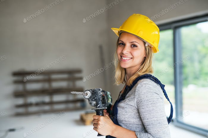Young woman worker with a yellow helmet and electric drill on the construction site.
