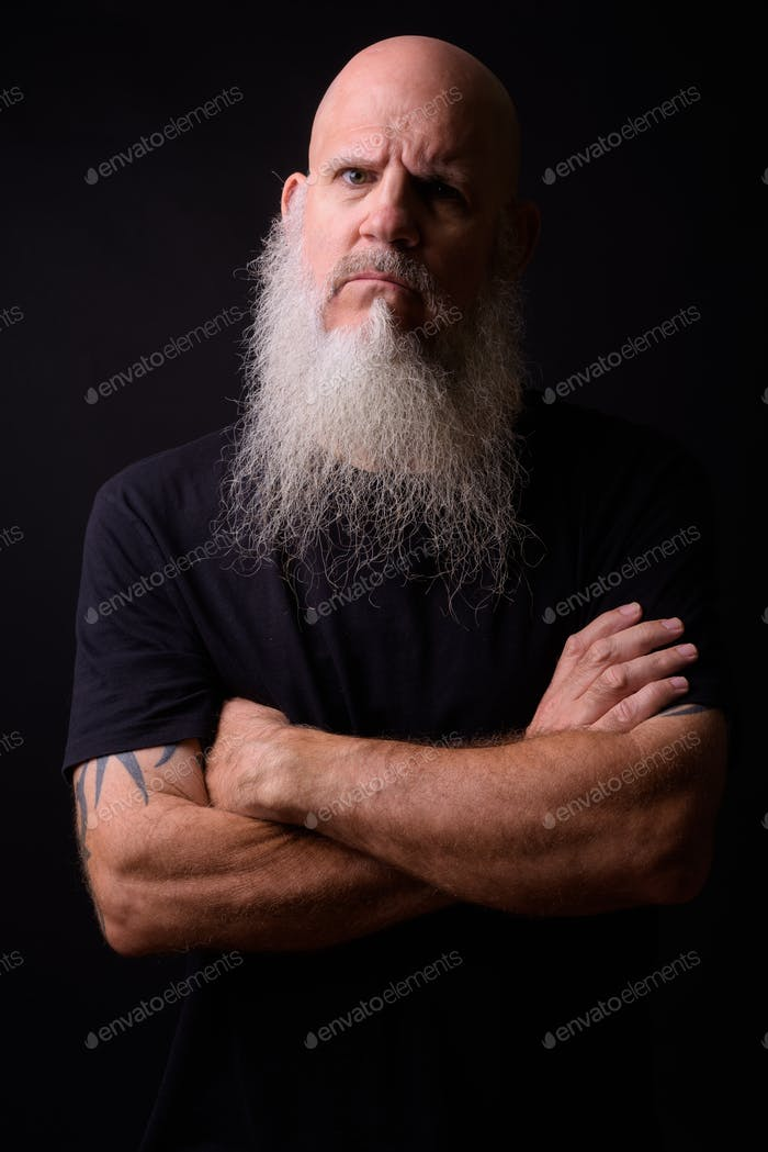 Mature bald bearded man against black background