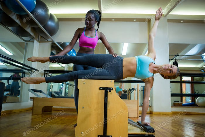 Trainer assisting woman with wunda chair in fitness studio