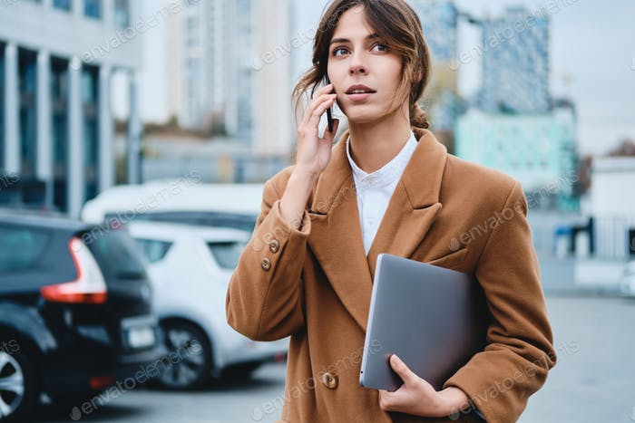Pensive businesswoman in coat with laptop talking on cellphone intently looking away on city street