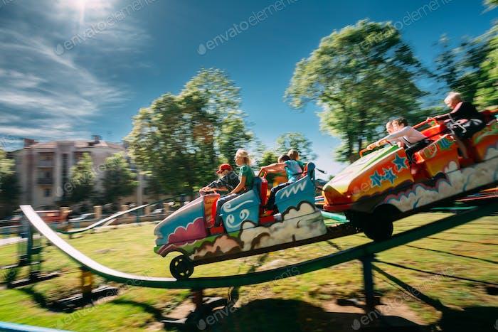 Menschen mit Spaß auf Achterbahn im Park. Foto mit Zoom-Unschärfe