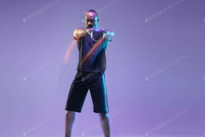 Young african-american bodybuilder training over purple background in neon, mixed light