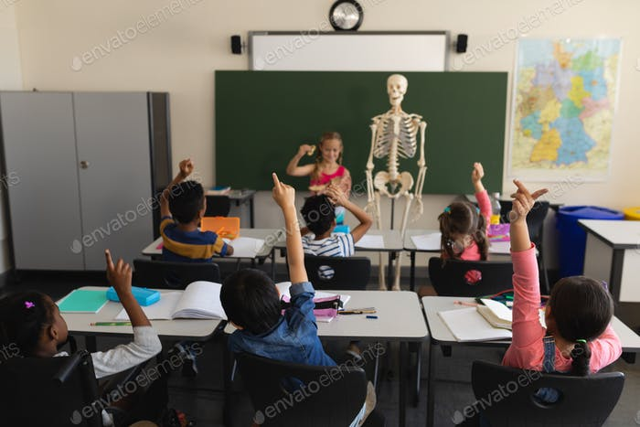 Rear view of schoolkids raising hands and sitting at desk in classroom of elementary school