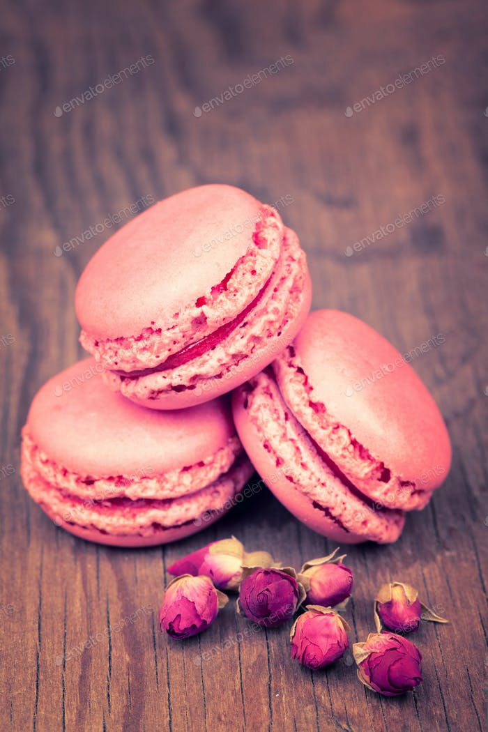 Macaroons with dry roses on retro vintage wooden background
