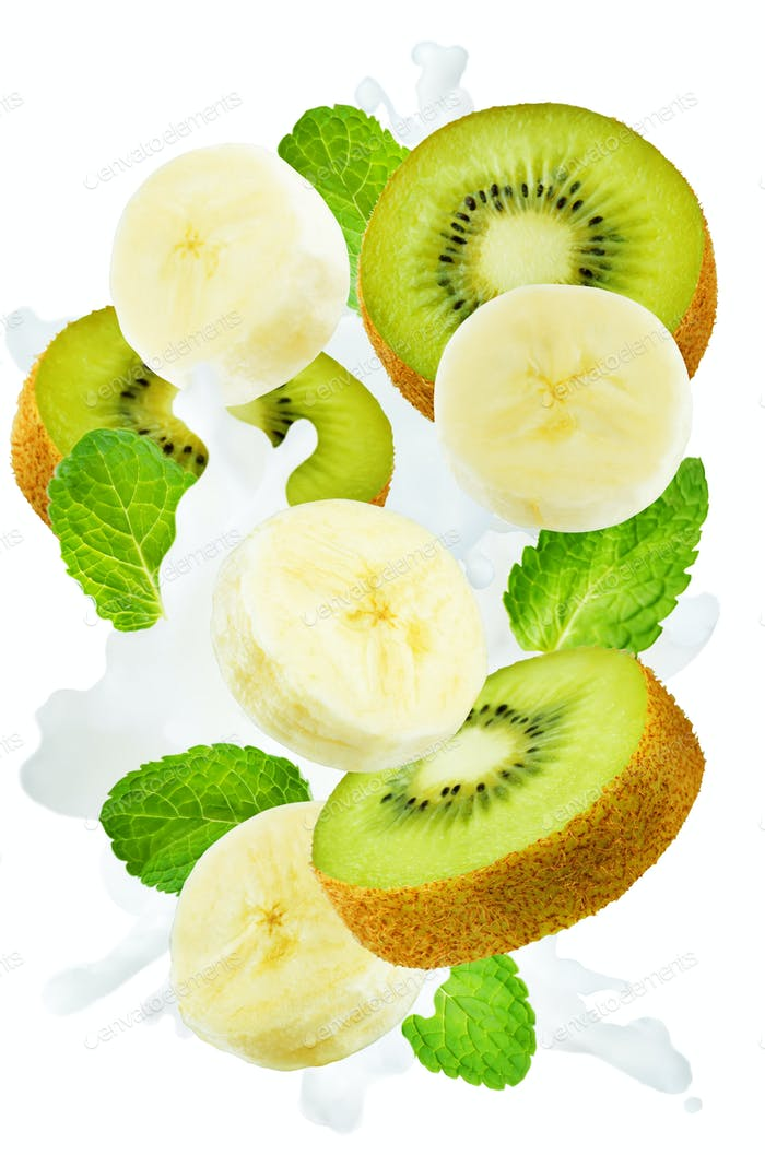 Flying kiwi and banana with mint leaves and a spray of milk