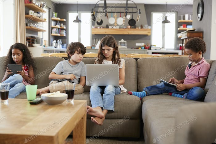 Group Of Children Sitting On Sofa Using Digital Devices