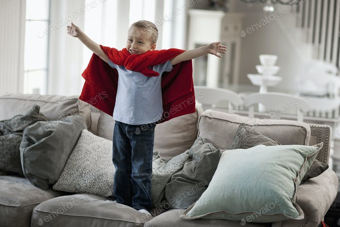 A child standing wearing a red cape, arms raised in a a superhero pose.