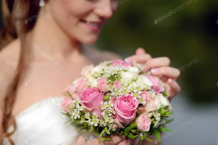 Beauty bride in bridal gown with bouquet and lace veil on the nature