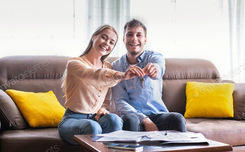 Lovely young girl with her boyfriend showing key to their new property indoors