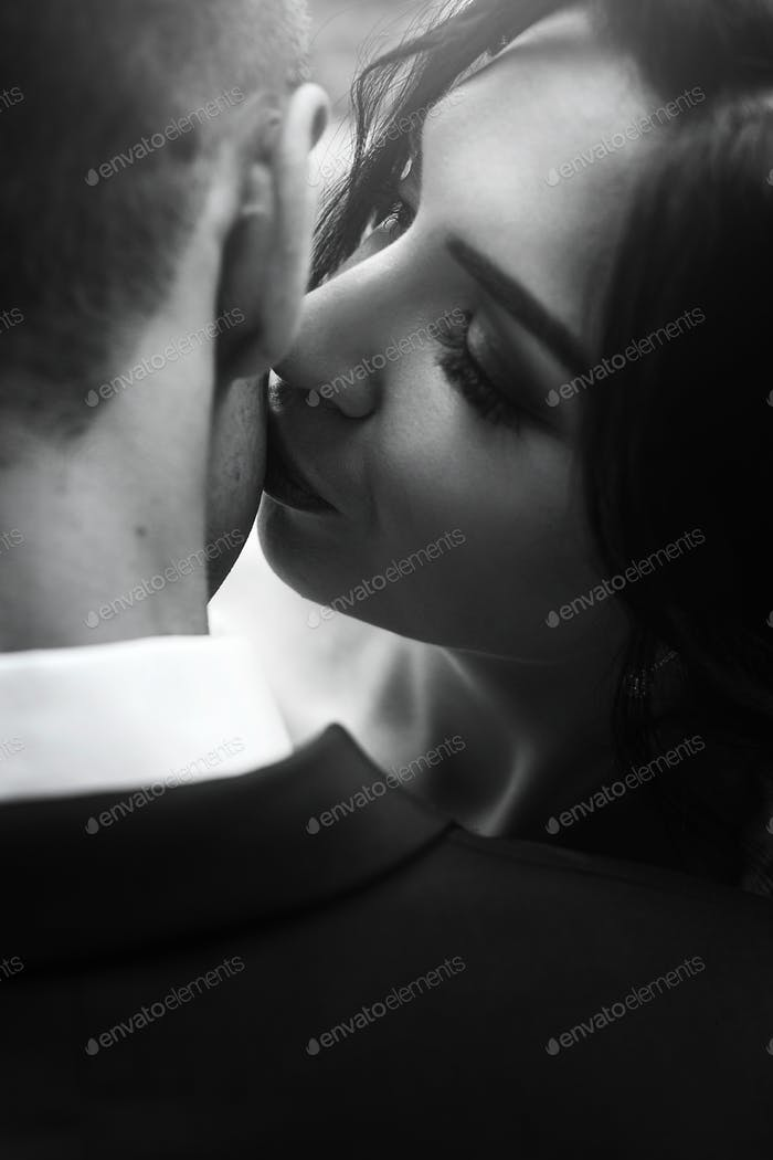 gorgeous happy bride kissing handsome groom in neck