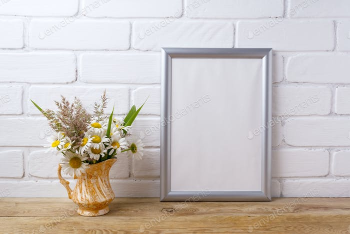 Silver frame mockup with chamomile and grass in golden pitcher