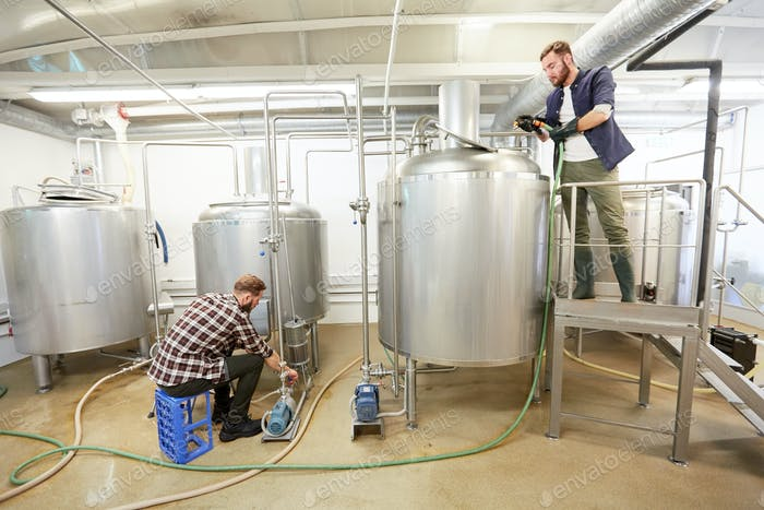 men working at craft beer brewery kettles
