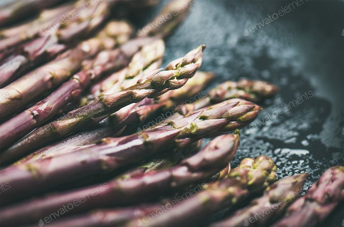 Fresh raw uncooked purple asparagus over dark background, horizontal composition