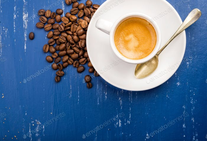 Tasse Espresso Kaffee und Bohnen auf hölzernen blau bemalten Tisch