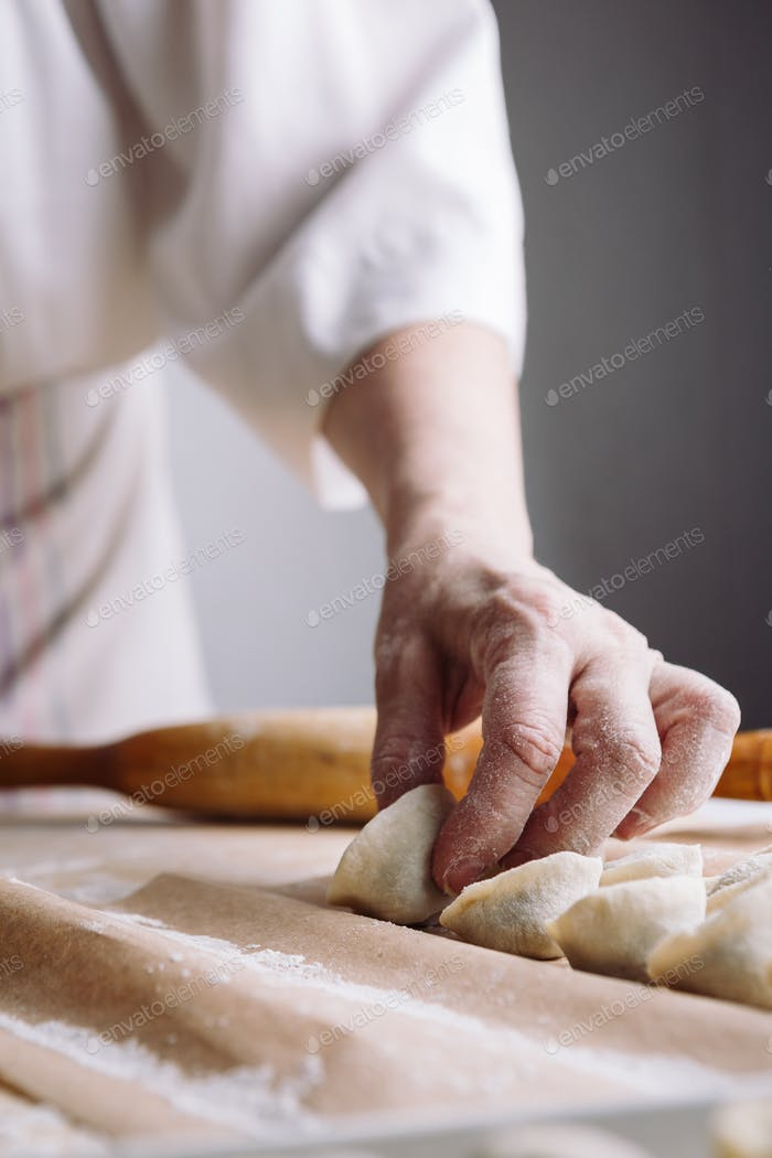woman folds the raw dumplings on a sheet of parchment