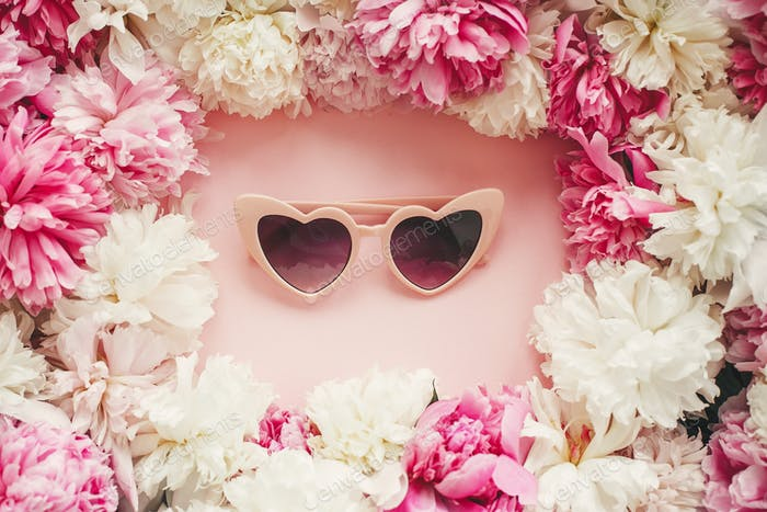 Pink heartshaped sunglassess in stylish pink and white peonies frame on pink paper