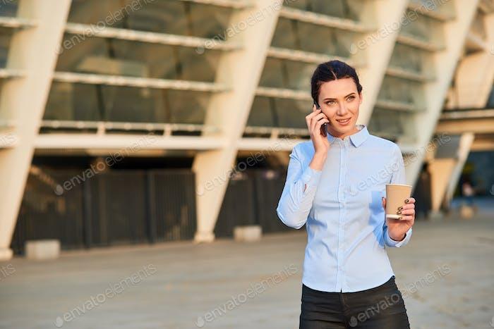 Geschäftsfrau hält Telefon und Pokal