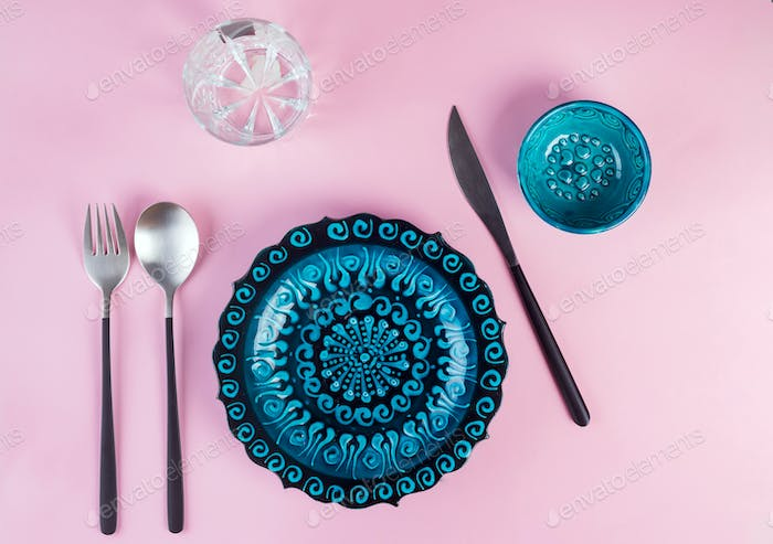 Turkish ceramics decorated blue plate with new luxury black cutlery on pink background, top view