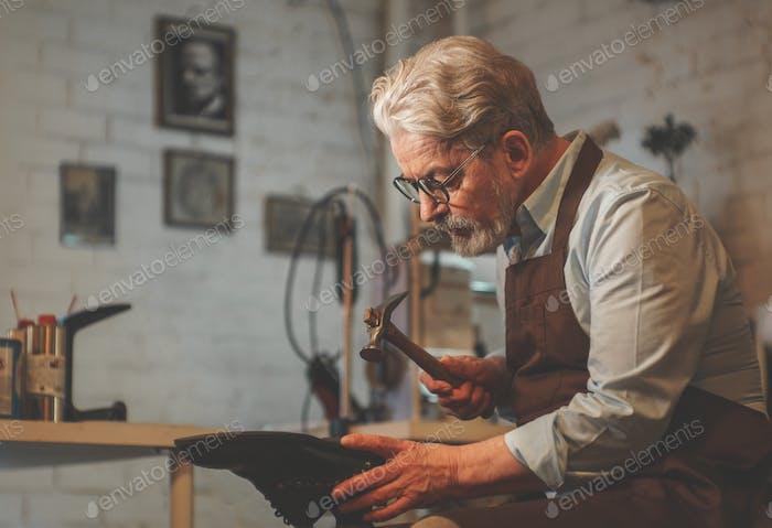 Ein älterer Schuhmacher in der Werkstatt