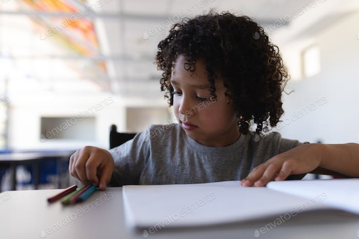 Front view of schoolboy studying at desk in classroom of elementary school