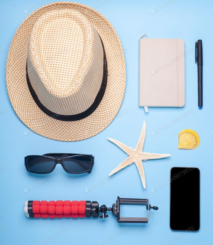 traveler accessories on blue background, top view