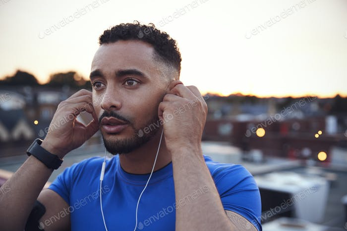 Male runner in urban setting adjusting earphones, close up