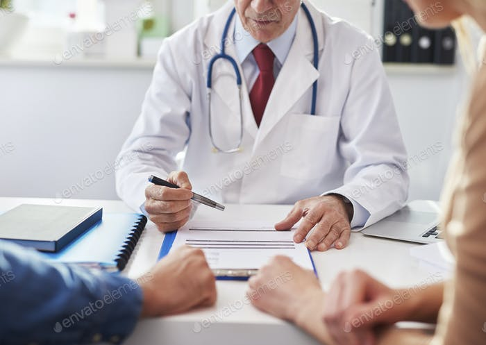 Doctor consulting prognosis with young couple